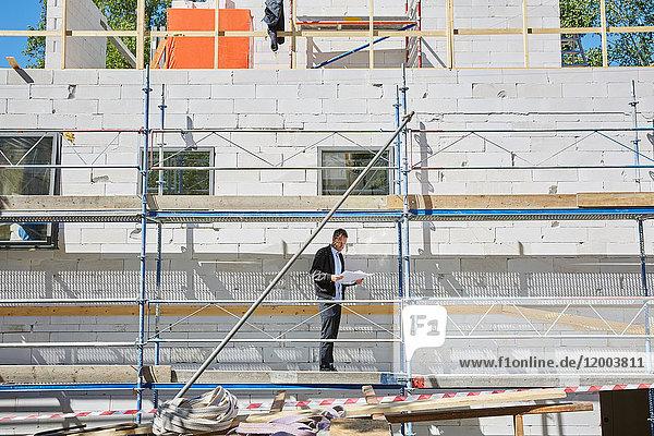 Volle Länge des männlichen Architekten mit Bauplan auf der Baustelle bei Sonnenschein