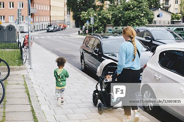Mutter schiebt Kinderwagen beim Gehen mit Sohn auf dem Bürgersteig in der Stadt
