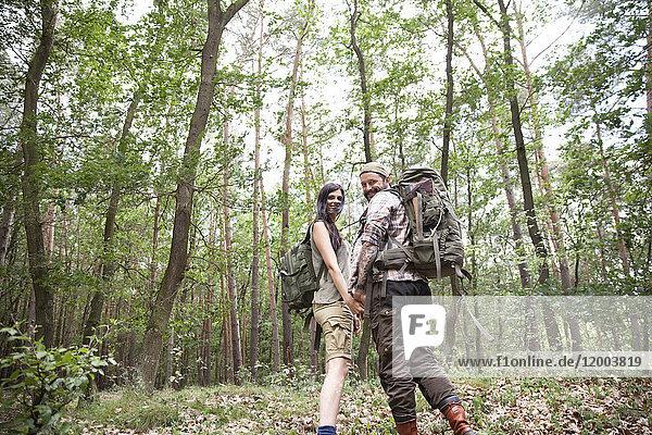 Glückliches Paar mit Rucksäcken auf einer Wanderung im Wald