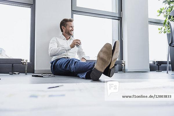 Entspannter Geschäftsmann sitzt auf dem Boden seines Büros bei einer Tasse Kaffee.