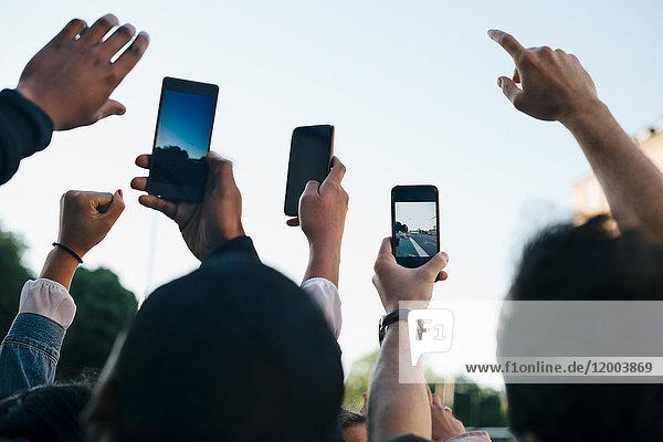 Low-Winkel-Ansicht von Freunden  die von Smartphones aus gegen den Himmel fotografieren.