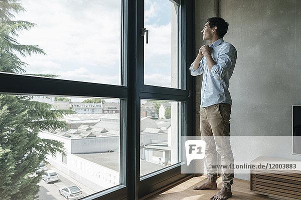 Junger Mann knöpfte sein Hemd zu und sah aus dem Fenster.