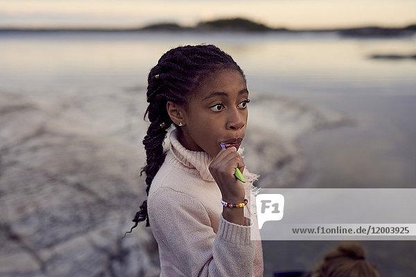 Mädchen beim Zähneputzen am Strand bei Sonnenuntergang