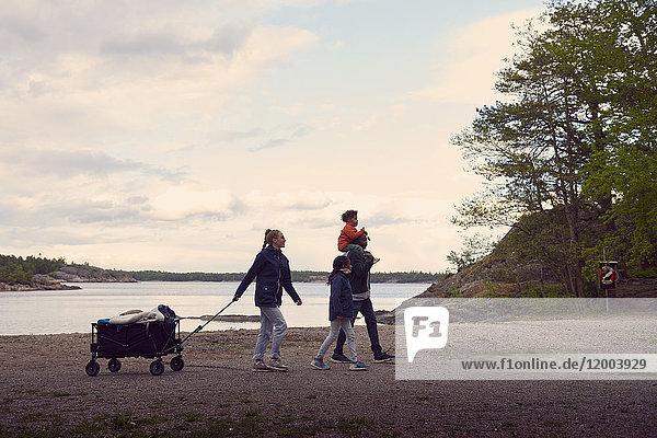 Frau beim Wandern mit der Familie am Strand gegen den Himmel.