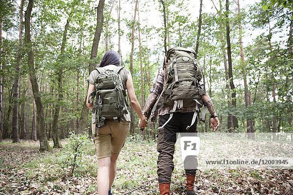 Paar mit Rucksäcken auf einer Wanderung im Wald