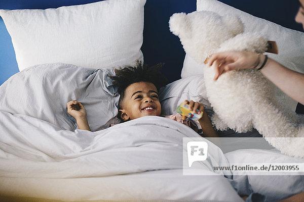 Lächelnder Junge schaut Mutter an  während er zu Hause auf dem Bett liegt.