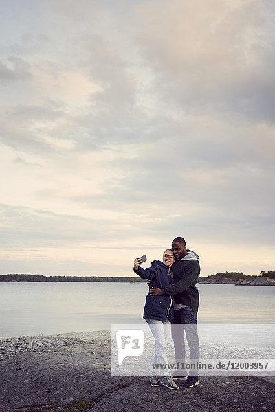 Lächelndes Paar  das sich beim Sonnenuntergang am Strand gegen den Himmel stellt.