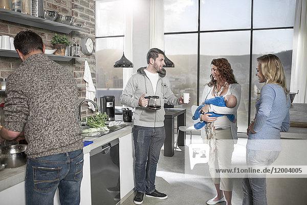 Familie und Freunde mit Baby und Kaffee in der Küche