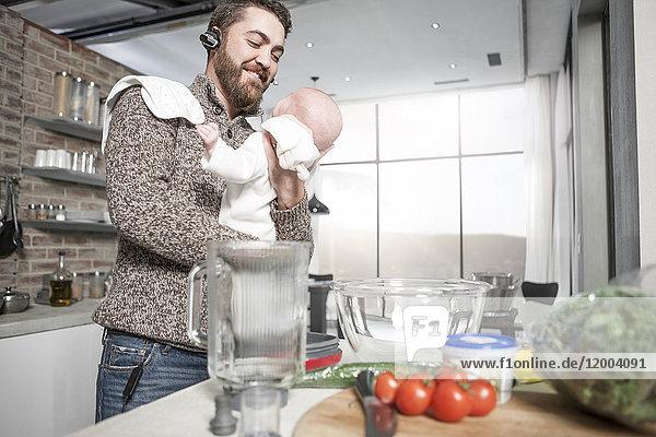 Vater mit Kopfhörer in der Küche hält Baby