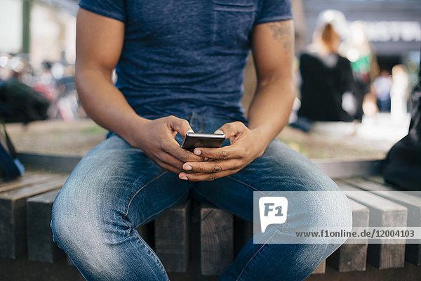 Mittelteil eines jungen Mannes  der ein Smartphone benutzt  während er auf einer Bank in der Stadt sitzt.