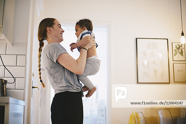Side view of smiling mother carrying son while standing at home