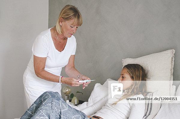 Großmutter untersucht die Temperatur der Enkelin im Schlafzimmer
