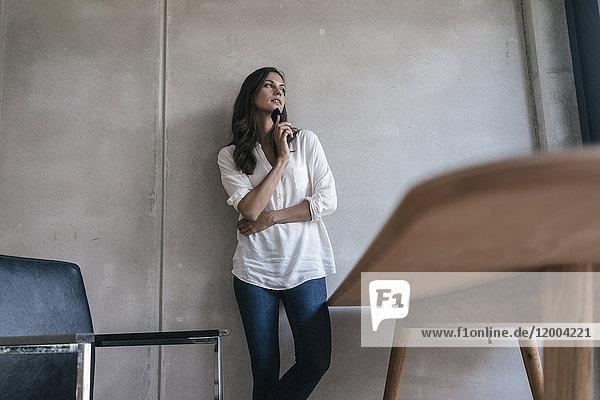 Nachdenkliche Frau mit Handy an der Betonwand