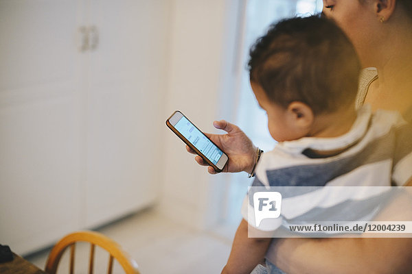 Mutter  die das Handy benutzt  während sie ihren Sohn zu Hause trägt.