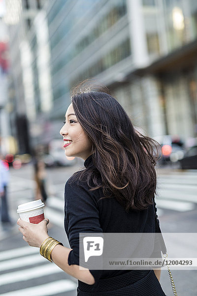 USA  New York City  Manhattan  smiling young woman with coffee to go crossing the street