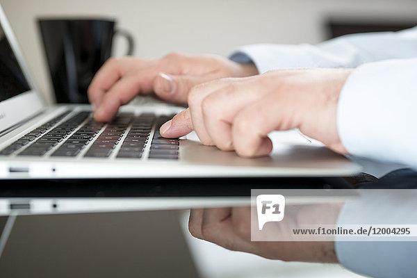 Mann sitzt am Schreibtisch und arbeitet mit seinem Laptop  Teilansicht