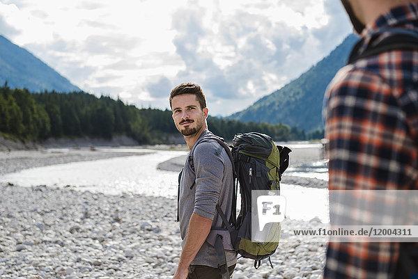 Deutschland  Bayern  Porträt eines jungen Wanderers mit Rucksack und Blick auf seinen Freund