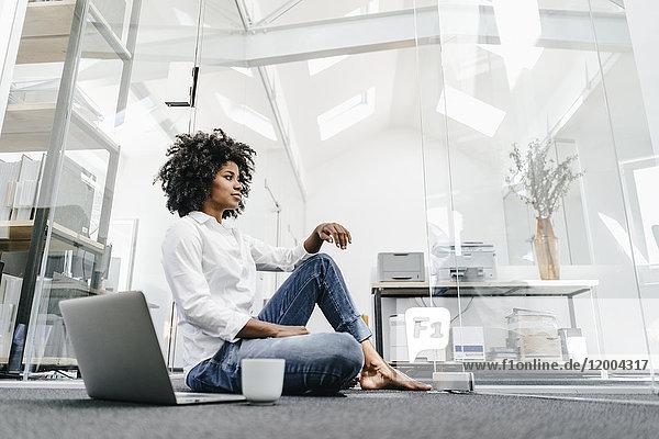 Junge Frau sitzt auf dem Boden im Büro mit Laptop