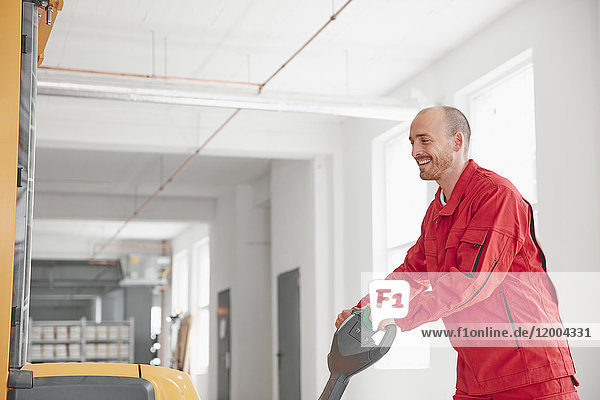 Smiling man in factory using forklift