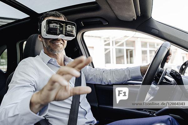 Geschäftsmann mit VR-Brille beim Autofahren