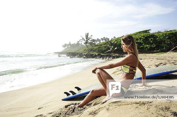 Frau am Strand mit Surfbrett