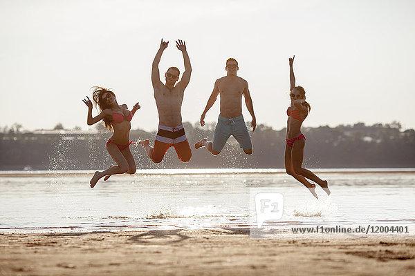 Glückliche Freunde beim Springen am Strand
