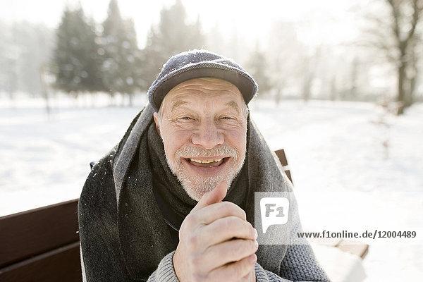 Porträt eines glücklichen älteren Mannes  der auf einer Bank in der Winterlandschaft sitzt.