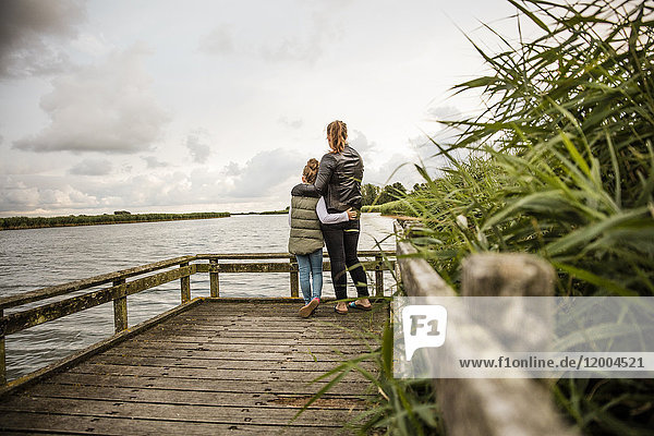 Mother and daughter standing on jetty at a lake