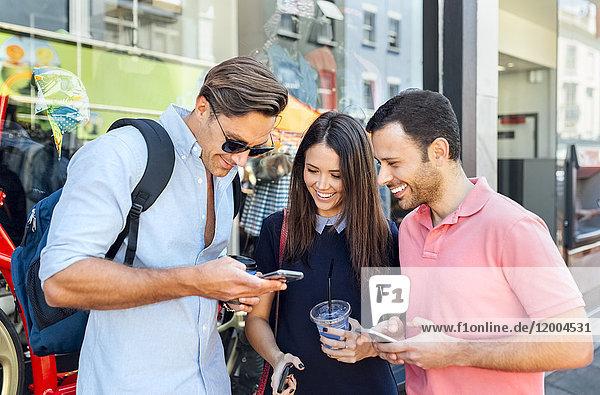 UK  London  Portobello Road  drei lächelnde Freunde beim Blick auf das Handy