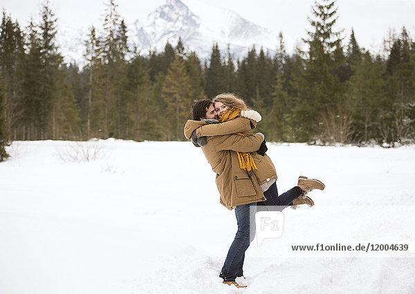 Glückliches junges Paar in verschneiter Winterlandschaft