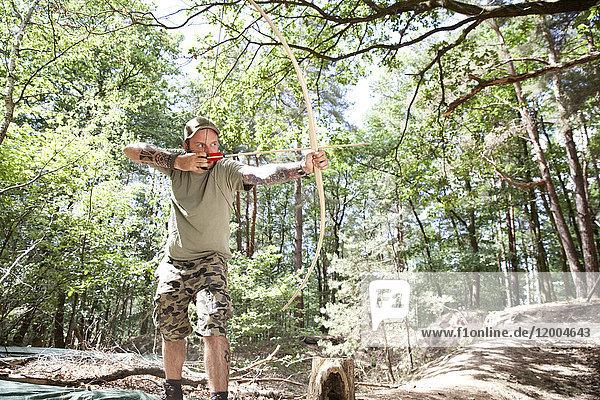 Mann schießt mit Pfeil und Bogen im Wald