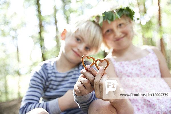Junge und Mädchen im Wald mit herzförmigem Brezelgebäck