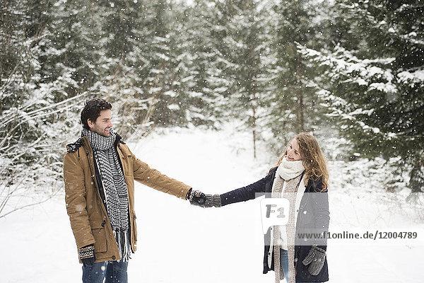 Glückliches junges Paar steht Hand in Hand in der Winterlandschaft und schaut sich an.