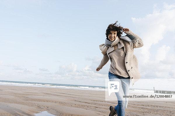 Glückliche Frau  die am Strand rennt.