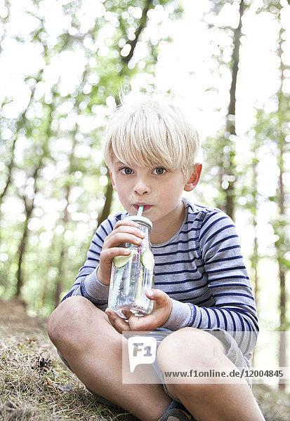 Junge  der aus einem Glas Wasser im Wald trinkt.