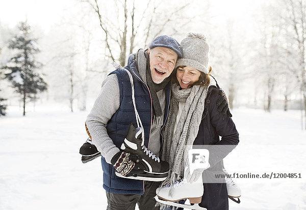 Glückliches Seniorenpaar mit Schlittschuhen in der Winterlandschaft