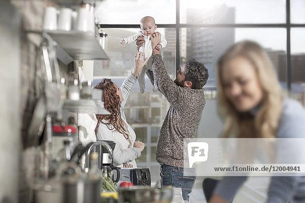 Mann und Frau heben das Baby in der Küche mit der Frau im Vordergrund auf