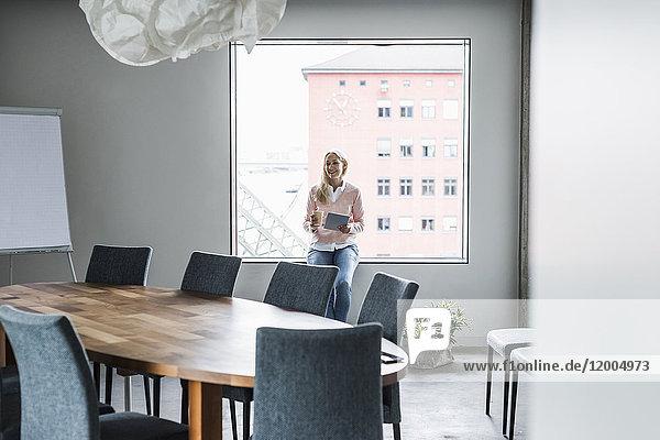 Lächelnde Geschäftsfrau im Konferenzraum am Fenster
