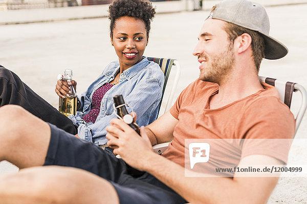 Junges Paar mit Bierflaschen auf dem Dach