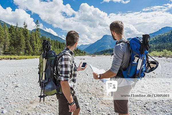 Deutschland  Bayern  zwei Wanderer stehen im trockenen Bachbett und orientieren sich mit Handy und Karte.