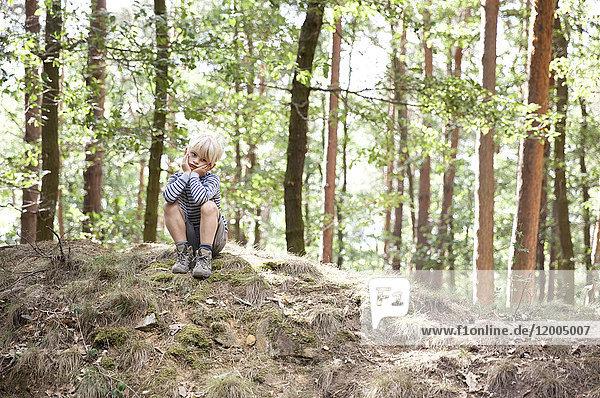 Junge im Wald sitzend auf Baumstumpf