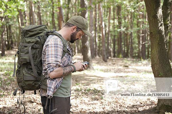 Mann mit Rucksack auf einer Wanderung im Wald per Handy