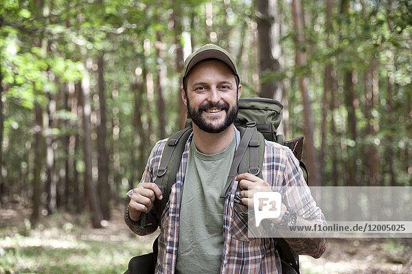 Porträt eines lächelnden Mannes mit Rucksack auf einer Wanderung im Wald
