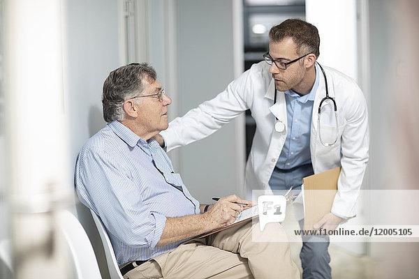 Arzt im Gespräch mit dem Patienten mit Akte in der Praxis