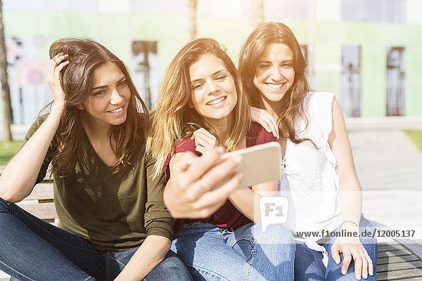 Drei glückliche Freundinnen  die mit einem Selfie nach draußen gehen.