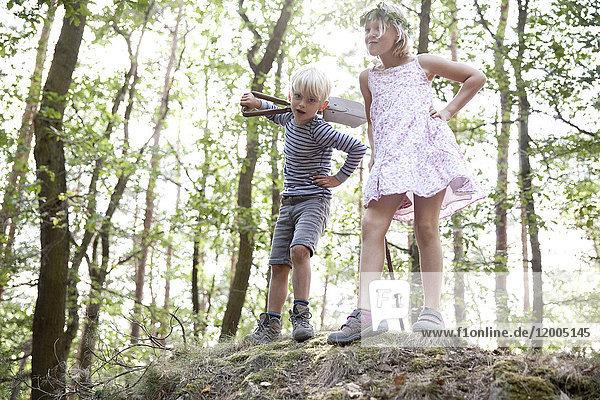 Junge und Mädchen stehen im Wald auf einem Hügel mit dem Spaten.