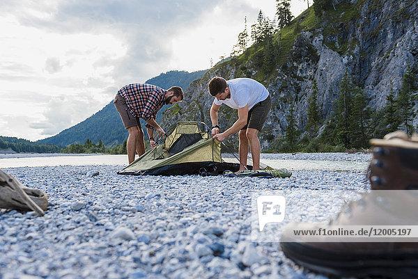 Deutschland  Bayern  zwei Wanderer beim Zelten auf Kiesbett