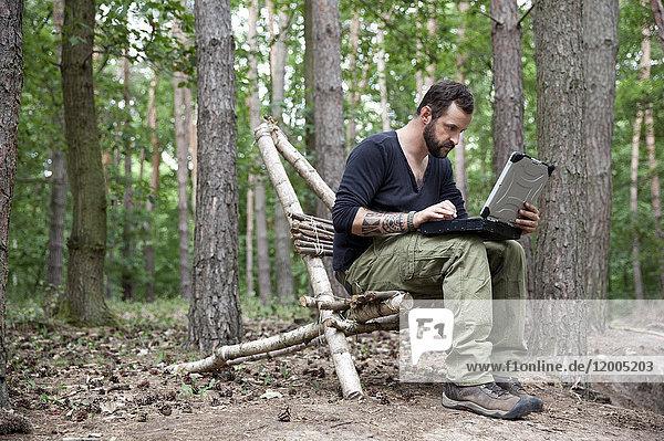 Mann sitzend auf selbstgemachtem Holzstuhl im Wald mit Laptop