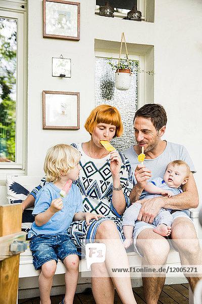 Familie sitzt auf dem Balkon und isst Eis am Stiel.