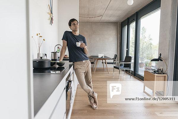 Junger Mann mit einer Tasse Kaffee in der Küche zu Hause